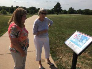 Carri Fry and Linda Slack look at the second stop on the StoryWalk